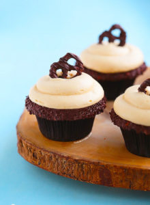 Peanut Butter Lava Fudge Cupcakes {Soft & tender chocolate cupcake filled with hot fudge sauce, frosted with a whipped, fluffy peanut butter frosting & topped with a chocolate covered pretzel}