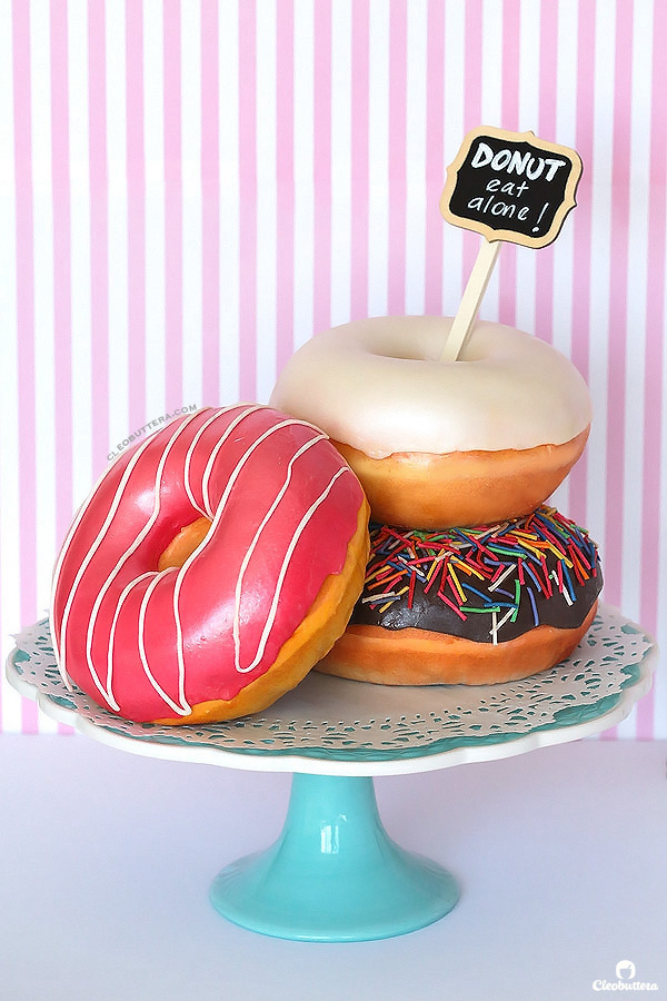 Donut Cake {3D sculpted, fondant covered, cake made to look like 3 different kinds of glazed donuts}.