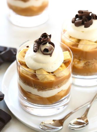 """The much loved banana toffee pie made even simpler in cute little individual cups! With layers of digestive biscuit crust, dulce de leche, banana slices and whipped cream, this no-bake """"pie"""" is dangerously delicious and a cinch to make!"""