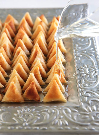 These tiny 'lil sweet treats will disappear off the plate in no time! Miniature crispy samosa wrappers filled with cream cheese and sweetened with a drizzle of thick sugar syrup. Good luck stopping at one!