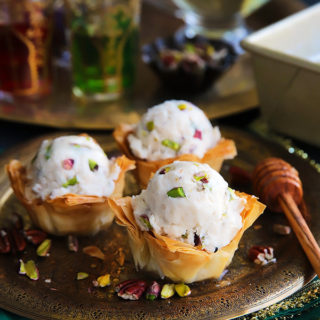 A fun summer spin on the Mediterranean favorite! Crispy phyllo cup sweetened with cinnamon honey syrup, topped with a scoop of an easy to make candied nuts cinnamon ice cream.