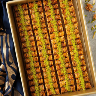 These bite-sized baklava rolls are made with scrunched layers of phyllo, a three nut mixture, cinnamon, spice and everything nice.  They're so good, it's difficult to stop at just one!