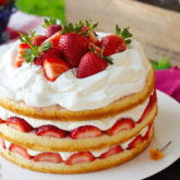 Three layers of soft and plush vanilla cake, infused with flavorful strawberry juice, topped with heaps of glazed fresh strawberries and swoops of thickened whipped cream that won't weep on you.