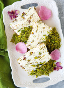 A show stopping ice cream cake with the much-loved flavors of the Middle East!  Scented eshta no-churn ice cream with nibs of caramelized pistachios, swirls of pistachio butter and a crown of green pistachio kunafa on top.  It is a pistachio lover dream come true and much easier to make than it seems.  Plus...recipe VIDEO at the end of the post!